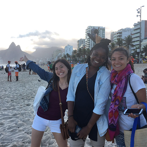 Three study abroad students on Rio beach at dusk