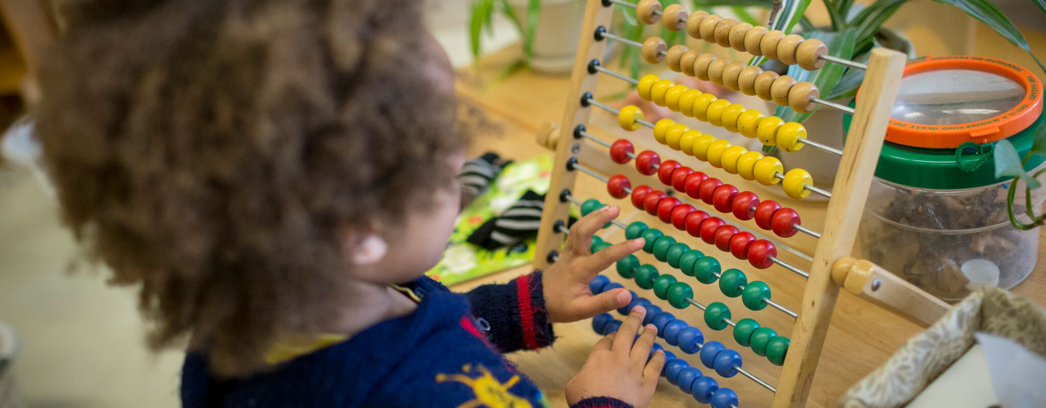A preschool student counts using an abacus.