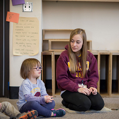 A teacher listens to a preschool student while they participate in a small group discussion